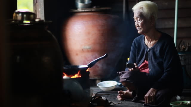 Pitiable Senior asian woman Sitting a Cooking Food video