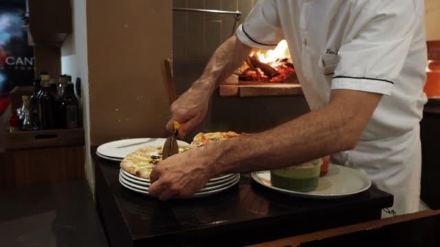 pizza chef preparing pizza at the restaurant - cultura italiana video stock e b–roll
