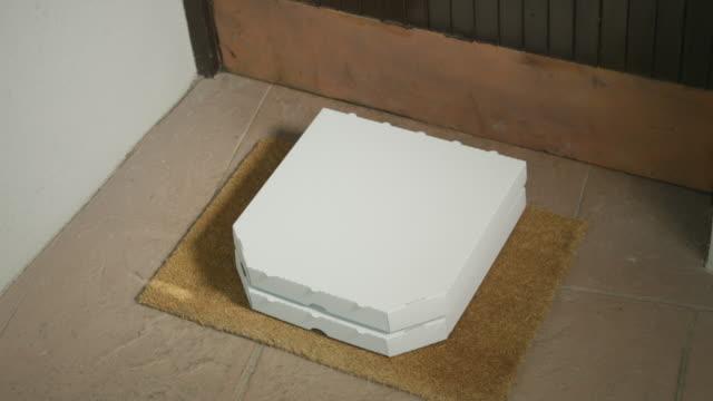 close up: pizza teslimat adam kapalı dairenin eşiğinde pizza bırakır. - sahanlık stok videoları ve detay görüntü çekimi