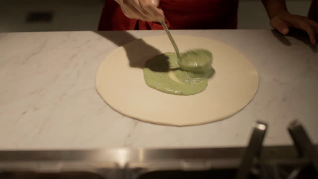 Pizza making Close up of human hands with a spoon putting pesto sauce on pizza sauce stock videos & royalty-free footage