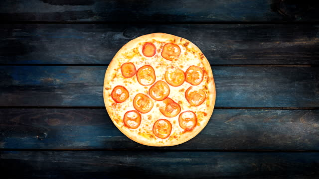 Pizza margarita with tomato slices rotating on a dark wooden background. Top view center orientation video