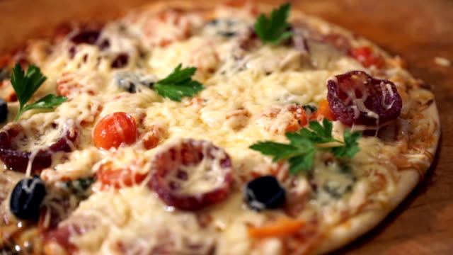 Pizza with ham, pepper, tomato and olives video