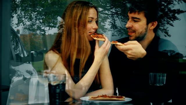 pizza, ungt par i en restaurang, fönster reflektioner. - dejta bildbanksvideor och videomaterial från bakom kulisserna