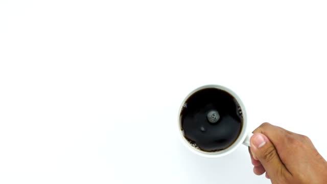 vídeos y material grabado en eventos de stock de lugar una taza de café negro, parte superior ver tabla blanca con mano - café negro