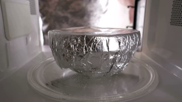 Placing bowl food covered with aluminum foil in the microwave oven