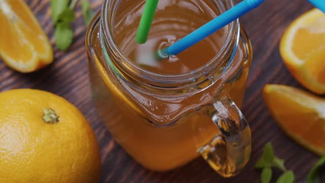 placera dricka halm i apelsinjuice i mason burk - konserveringsburk bildbanksvideor och videomaterial från bakom kulisserna