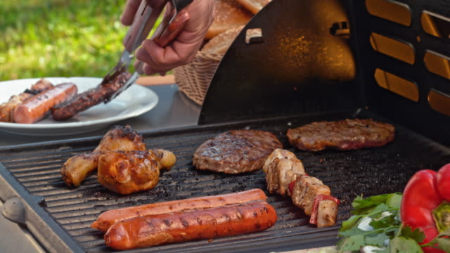 Placing meat from the grill onto a plate Close up handheld shot of male hand placing meat from the grill onto a plate with tongs. grilling stock videos & royalty-free footage