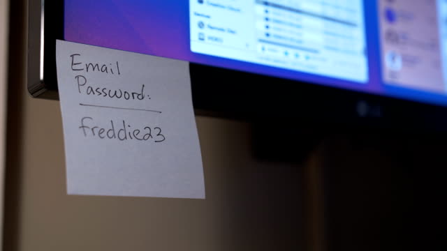 Placing Password Reminders on a Computer Monitor A person places Post-It password reminders on a computer monitor. password stock videos & royalty-free footage