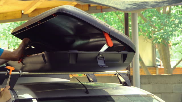 Placing the summer vacation chairs on roof rack on car with the cargo box
