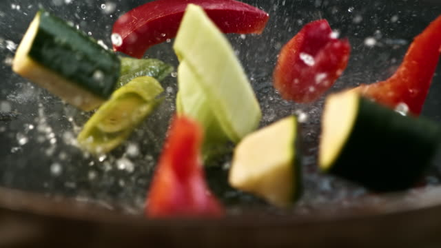 SLO MO placing vegetables into a hot pan Slow motion close up shot of vegetables being added into a hot pan and they are bouncing on a hot surface. cooking pan stock videos & royalty-free footage