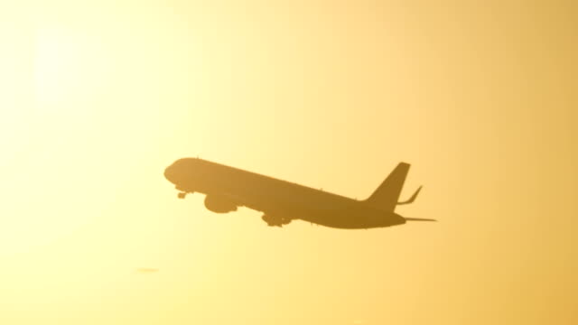 Plane flying in evening sky against sun flare Black silhouette of the airplane ascending in golden sunset sky against bright sunshine plane stock videos & royalty-free footage
