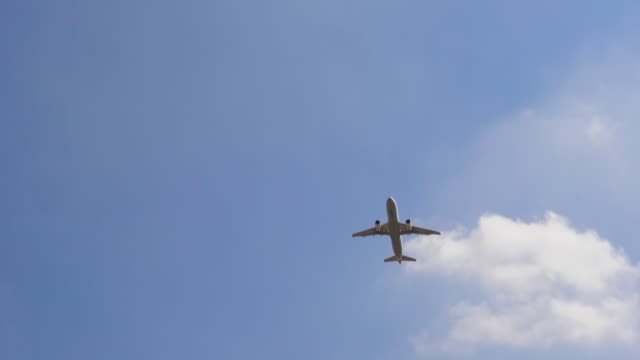 Plane flying over head on blue sky, 4к. Airplane takeoff into the sky.