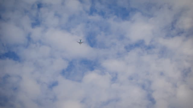 Plane is flying at a high altitude in the sky. Aircraft flies into the distance among a large number of nearly transparent clouds video