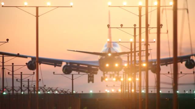 vídeos de stock, filmes e b-roll de avião pousando no pôr-do-sol - avião