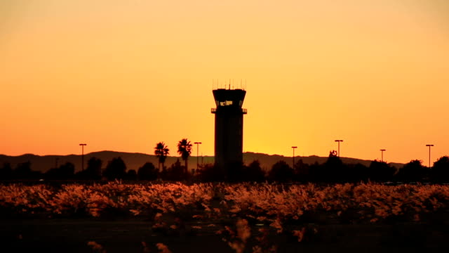 Plane takes off at sunset by air traffic tower video