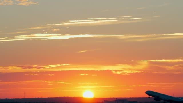 vídeos de stock e filmes b-roll de plane taking off at golden sunset - remover