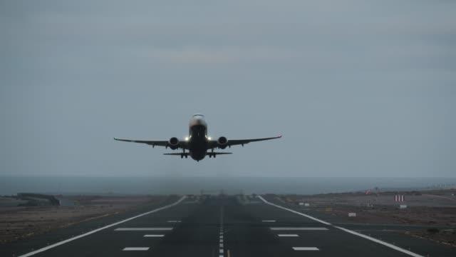 Plane taking off from runway overlooking the ocean