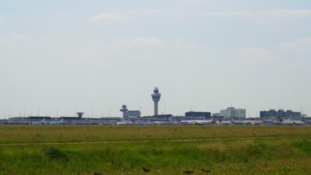stockvideo's en b-roll-footage met vliegtuigen die vertrekken en aankomen op schiphol airport gezien vanaf een afstand, amsterdam, nederland, juni 21nd 2019 - schiphol