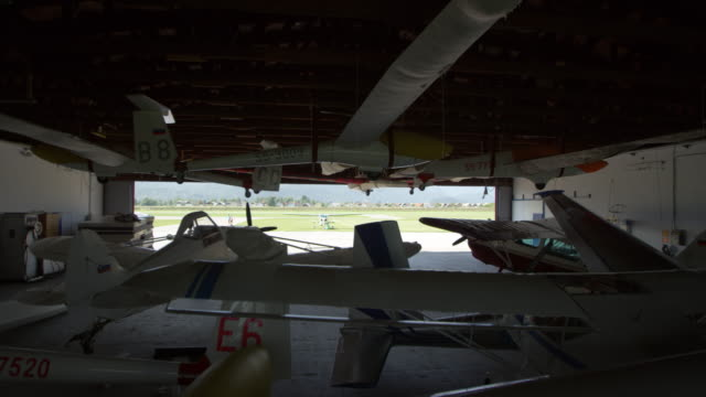CS Planes parked in the hangar and two men opening the hangar door