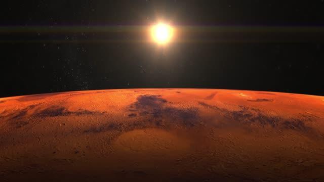 planeten mars från rymden. stjärnor blinka. flyg över mars. 4 k. sunrise. planeten mars roterar långsamt. solen är i ramen. kameran flyttas framåt. - mars bildbanksvideor och videomaterial från bakom kulisserna