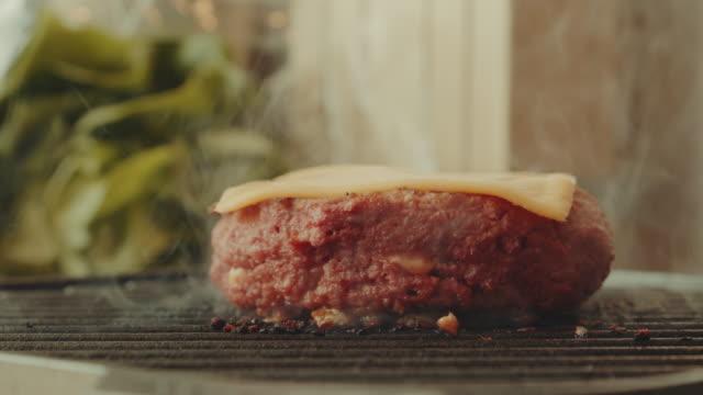 vídeos de stock e filmes b-roll de a plant based, non-meat, vegan burger grilled at high temperature - meat texture