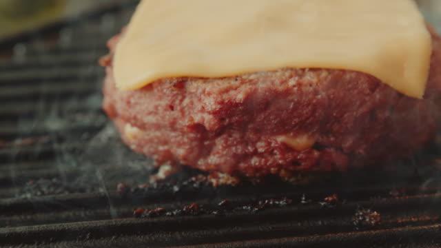 vídeos de stock e filmes b-roll de a plant based, non-meat, vegan burger on a cast iron grill - meat texture