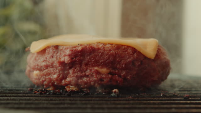 vídeos de stock e filmes b-roll de a plant based, non-meat, vegan burger with cheese being cooked - meat texture
