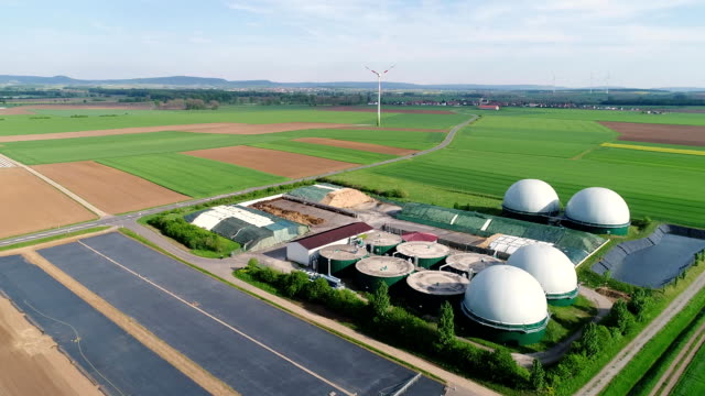 Plant for the production of biogas in the green field, plant for the production of biogas against the background of wind generators view from above Camera flight over biogas plant from pig farm. Renewable energy from biomass. Modern agriculture European Union. aerial view, panoramic view from the air. biomass renewable energy source stock videos & royalty-free footage