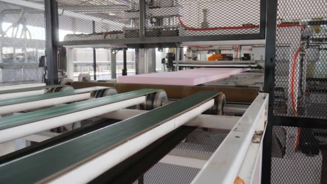 plant with equipment for production foam polystyrene, automatic cutting of styrofoam on conveyor line - poliuretano polimero video stock e b–roll