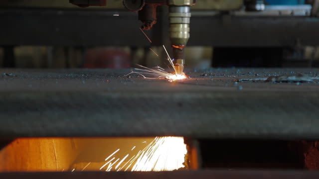 Plasma cutting of metal with a cnc. A plasma cutter cuts a workpiece from a sheet of metal. Laser cutter in production. Laser-cutting equipment is making incisions on metal video