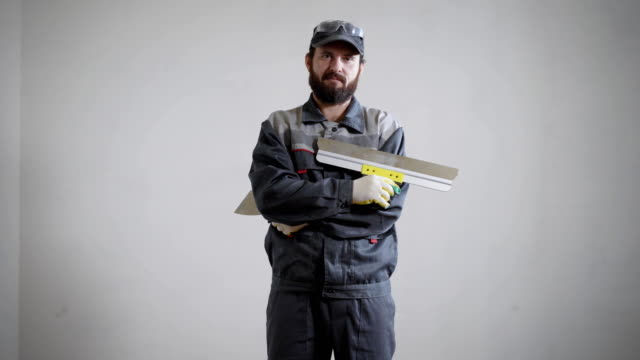 plasterer is standing on a white wall background in apartment and holding spatula and big putty knife plasterer is wearing work clothes is standing on a white wall background in apartment and holding spatula and big putty knife, looking at a camera house painter stock videos & royalty-free footage