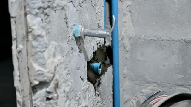 Plasterer plastering on brick wall in bathroom