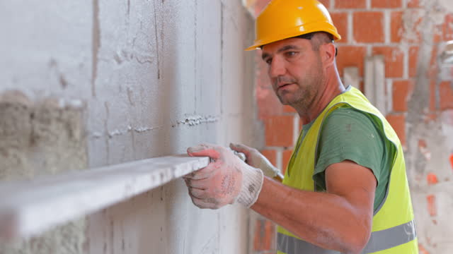Plasterer using a level to check the plaster layer on the wall