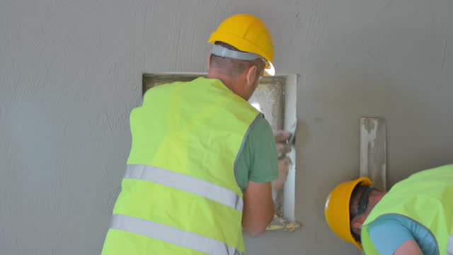 LD Plasterer working on the plaster around a window