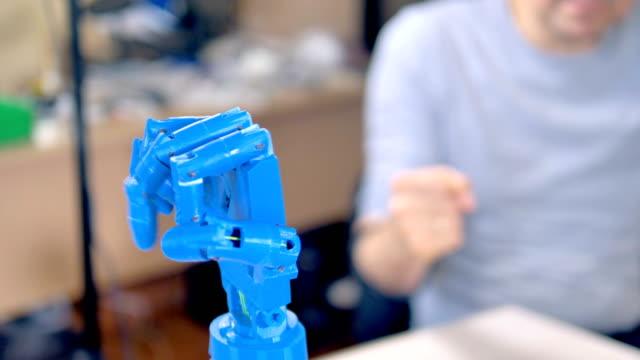 un braccio bionico blu plastico muove le dita. - rivoluzione industriale video stock e b–roll