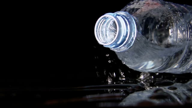 SLOW: A plastic bottle falls on a black table and water pours from it video
