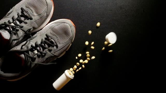 doping: hap ile plastik şişe bir spor ayakkabıları yakın düşüyor-yavaş hareket, üst görünüm - doping stok videoları ve detay görüntü çekimi