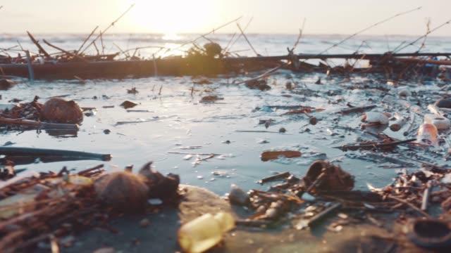 plastflaskor, väskor och andra sopor dumpade på svarta stranden och i havet. miljöföroreningar problem koncept. - plastic ocean bildbanksvideor och videomaterial från bakom kulisserna