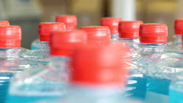 Plastic bottles filled with blue liquid, move along the conveyor belt. 4K. Plastic bottles filled with blue liquid, move along the conveyor belt. dishwashing liquid stock videos & royalty-free footage