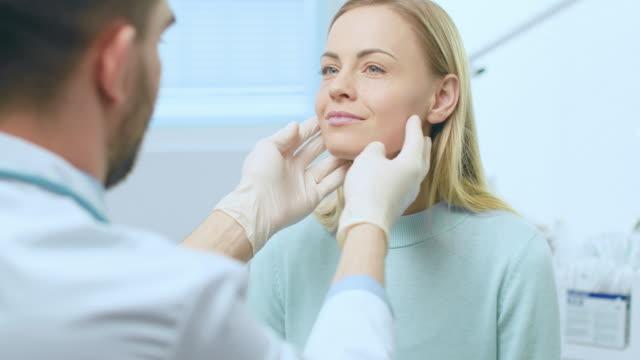 kunststoff / kosmetische chirurgen untersucht schöne frau ins gesicht, berührt es mit behandschuhten händen, inspektion falten für die zukunft-facelift-operation. - kosmetik beratung stock-videos und b-roll-filmmaterial