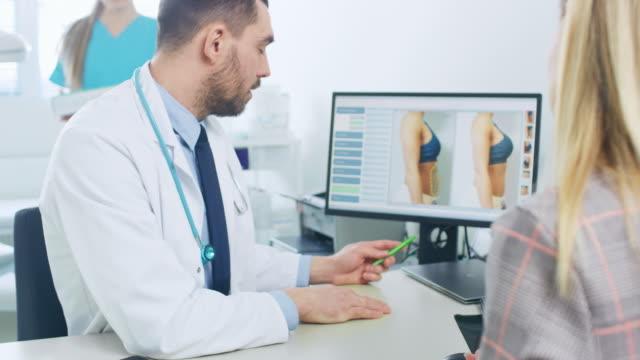 kunststoff / kosmetische chirurgen zeigt weibliche patienten mögliche ergebnisse der fettabsaugung, er punkte auf computerbildschirm zeigt reduktion des fettgewebes auf dem bauch. - menschlicher verdauungstrakt stock-videos und b-roll-filmmaterial