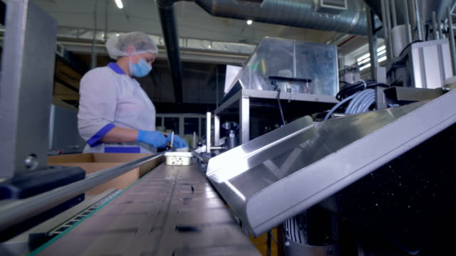 Plastic curd containers move on factory lie to a worker. video