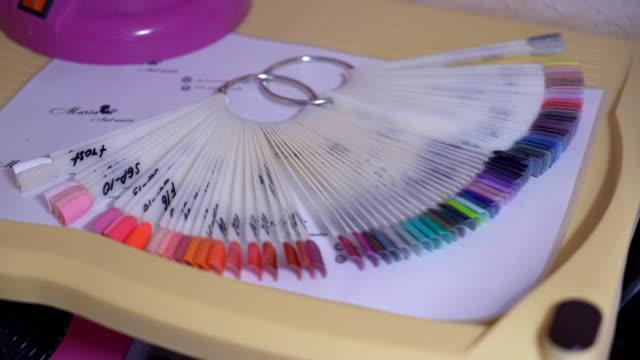 vidéos et rushes de palette en plastique avec les ongles artificiels. grand choix de couleurs de vernis à ongles. fullhd - sky