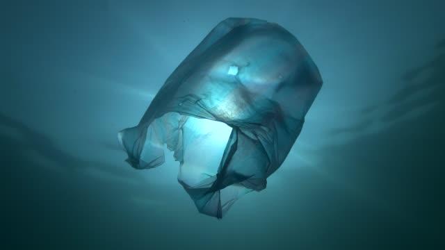 plastföroreningar, blå plastpåse sakta driver under vattnet i solens strålar. låg vinkel skott, contre-jour. plast skräp under vatten. plast sopor miljöförorening problem - plastic ocean bildbanksvideor och videomaterial från bakom kulisserna