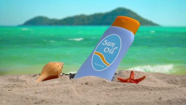 plastic sun oil bottle on the beach at sunset. - sun cream stock videos & royalty-free footage