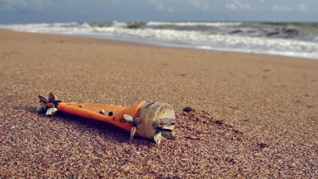 vidéos et rushes de pollution en plastique de bouteille de lotion de suntan jetée sur la plage - bivalve