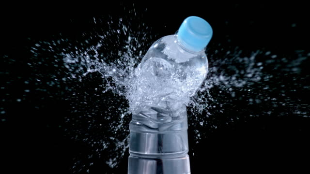 SLO MO LD Plastic water bottle being cut in half with one swing off a sharp knife