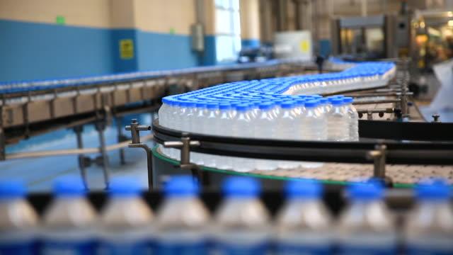 vídeos de stock, filmes e b-roll de garrafas plásticas de água em fábrica de produção de correia transportadora - garrafa