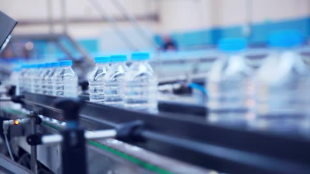 Plastic water bottles in factory on conveyor belt