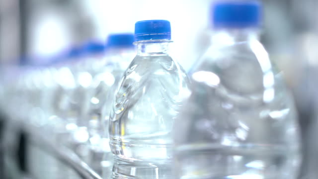 Plastic water bottles on conveyor and water bottling machine industry. video